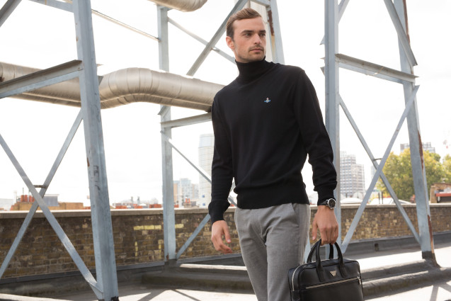 man in a black polo neck and grey trousers