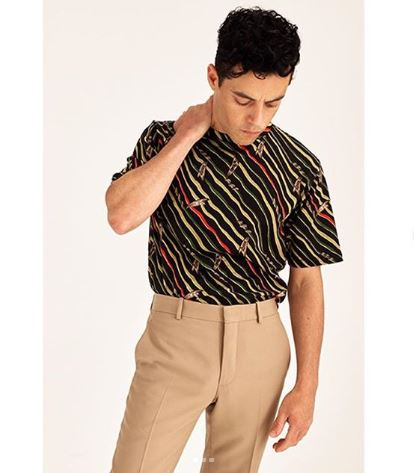 Malek Rami is stood with a hand on his neck wearing beige trousers and an 80s print shirt