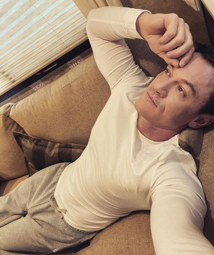 Luke Evans Lying on a coach wearing ahtleisurewear