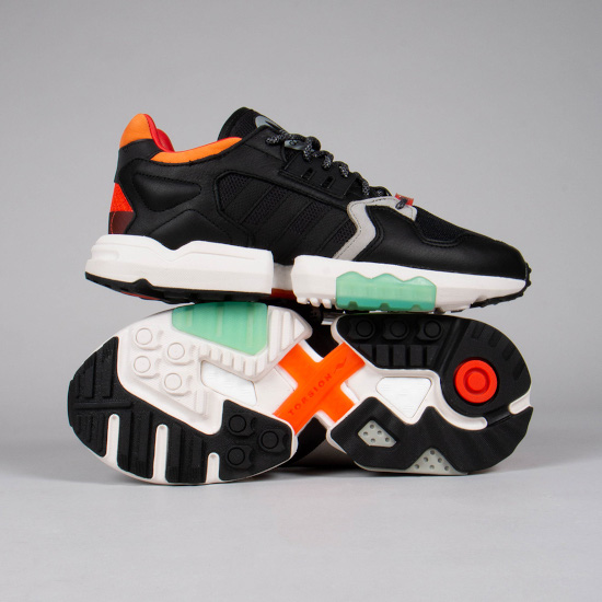 a bright pair of green, black and orange adidas trainers