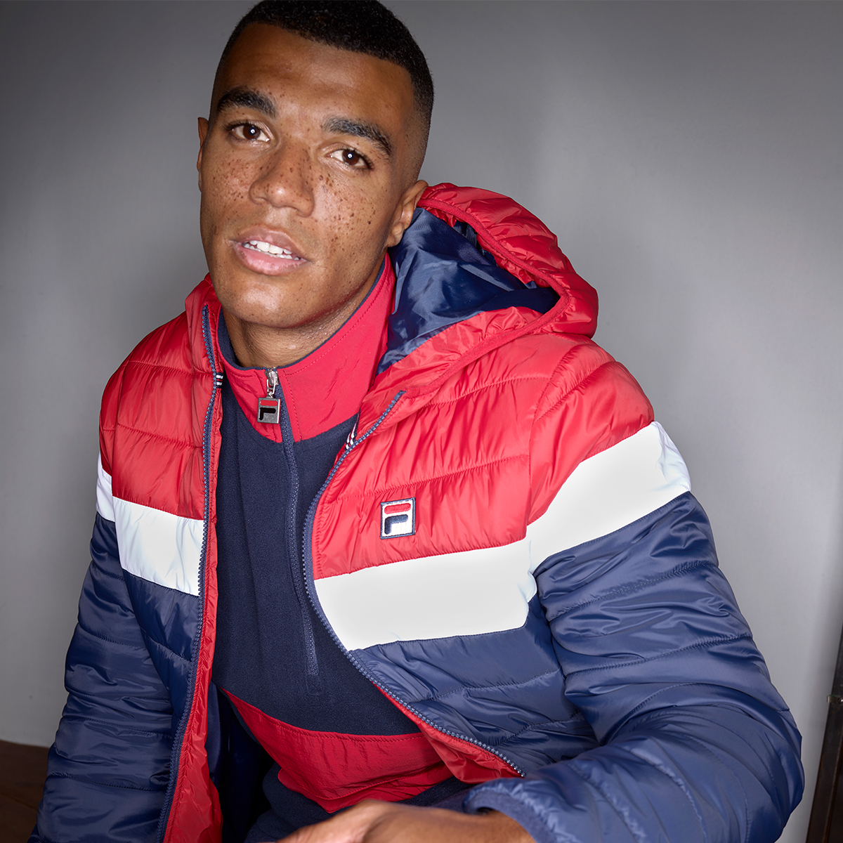 a man looks into the camera wearing a FILA tracksuits