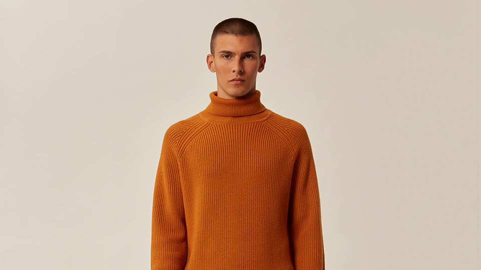 a man is stood wearing a orange ted baker jumper