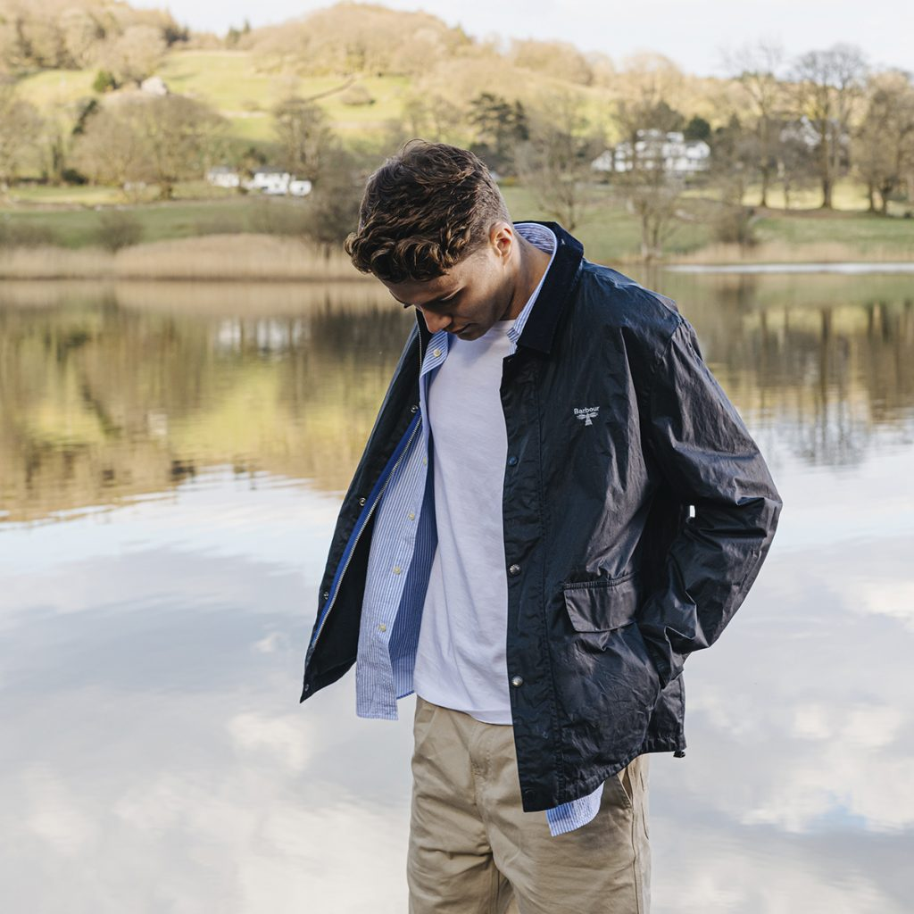 Man in Barbour Beacon jacket standing next to a lake