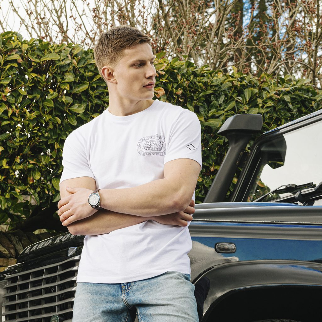 A man in a white t shirt and jeans leans against a Land Rover