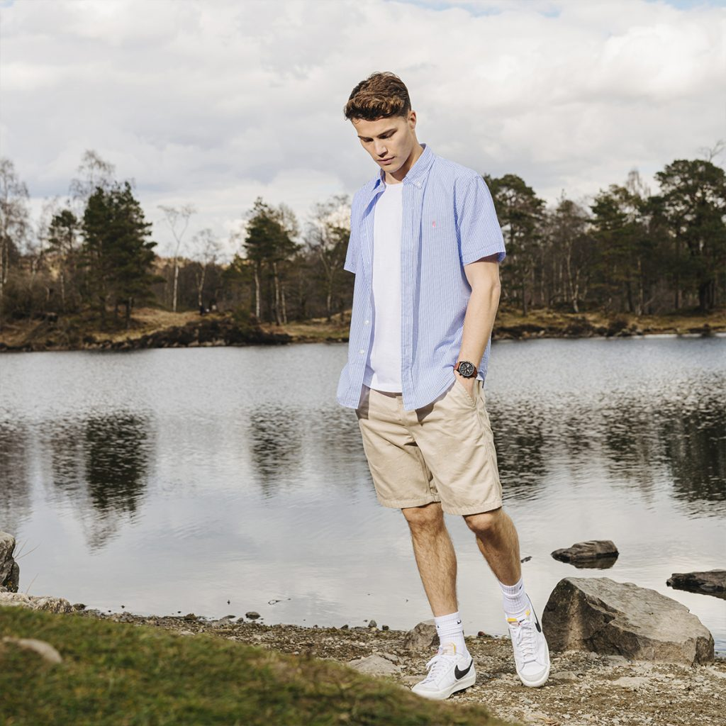 Man in Ralph Lauren shirt stands at the edge of a lake