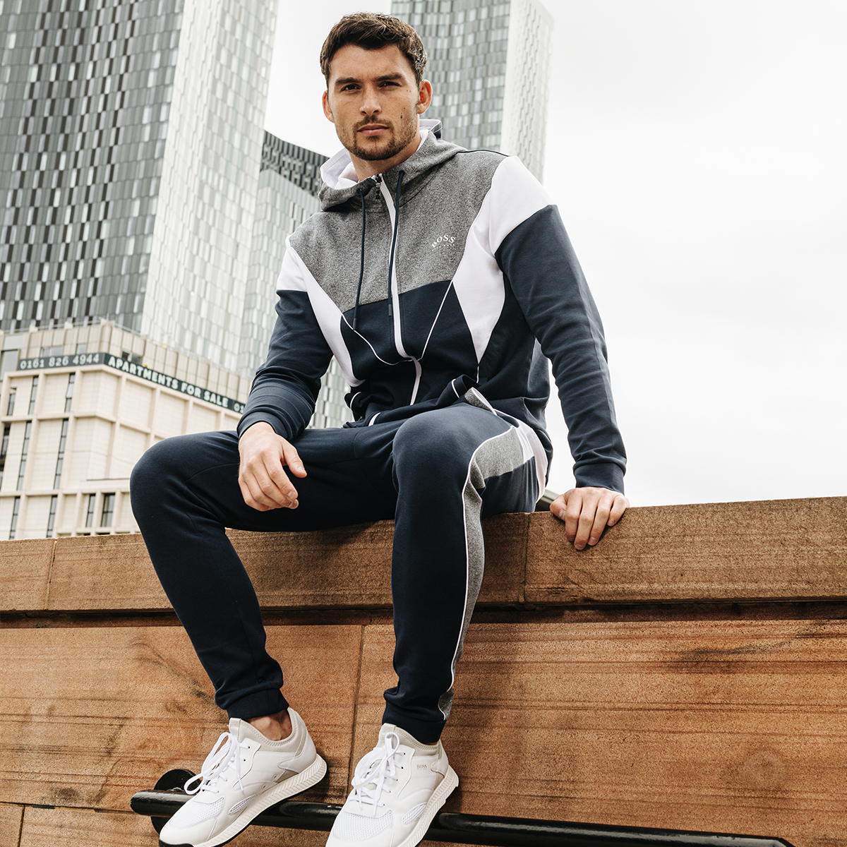 A man sitting in an urban setting wearing a BOSS Athleisure tracksuit.
