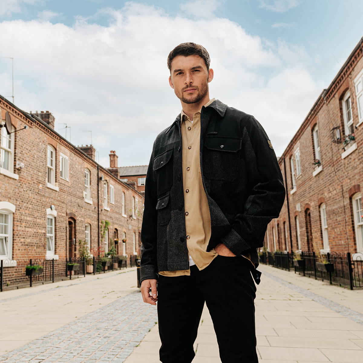 A man standing in a residential street wearing a Belstaff jacket and jeans