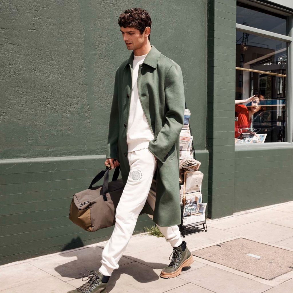 A man in white Ted Baker trousers and a long green coat walking down the street