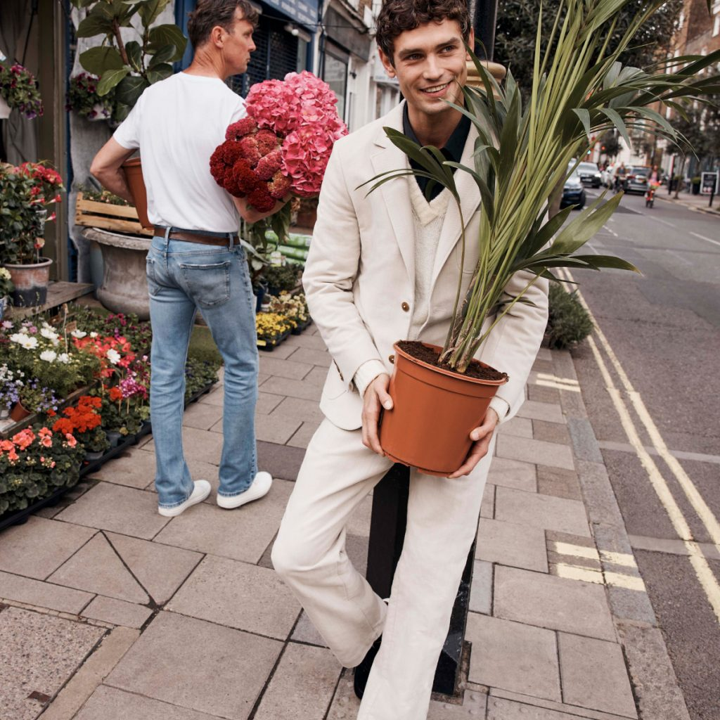 A smiling man dressed in a light coloured Ted Baker suit leaning against something while holding a houseplant