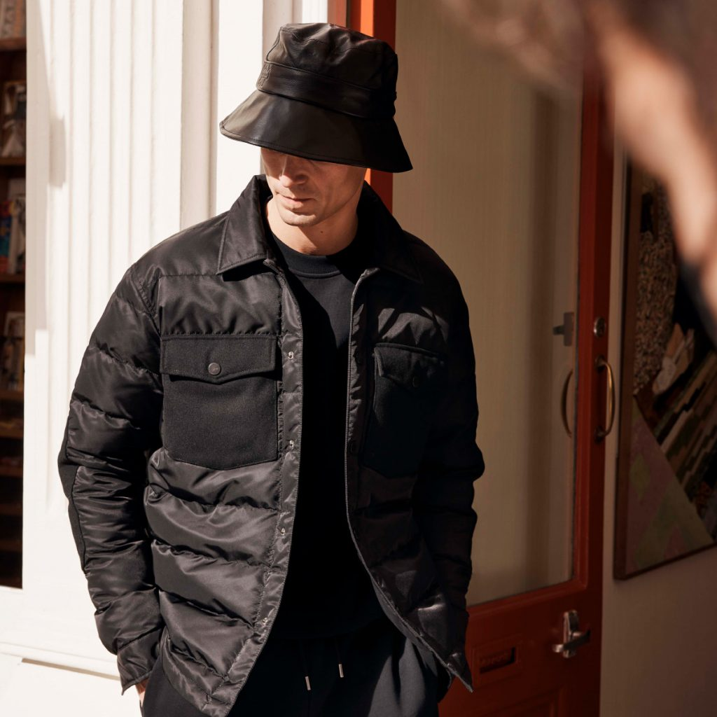 A man dressed in a black Ted Baker jacket and bucket hat