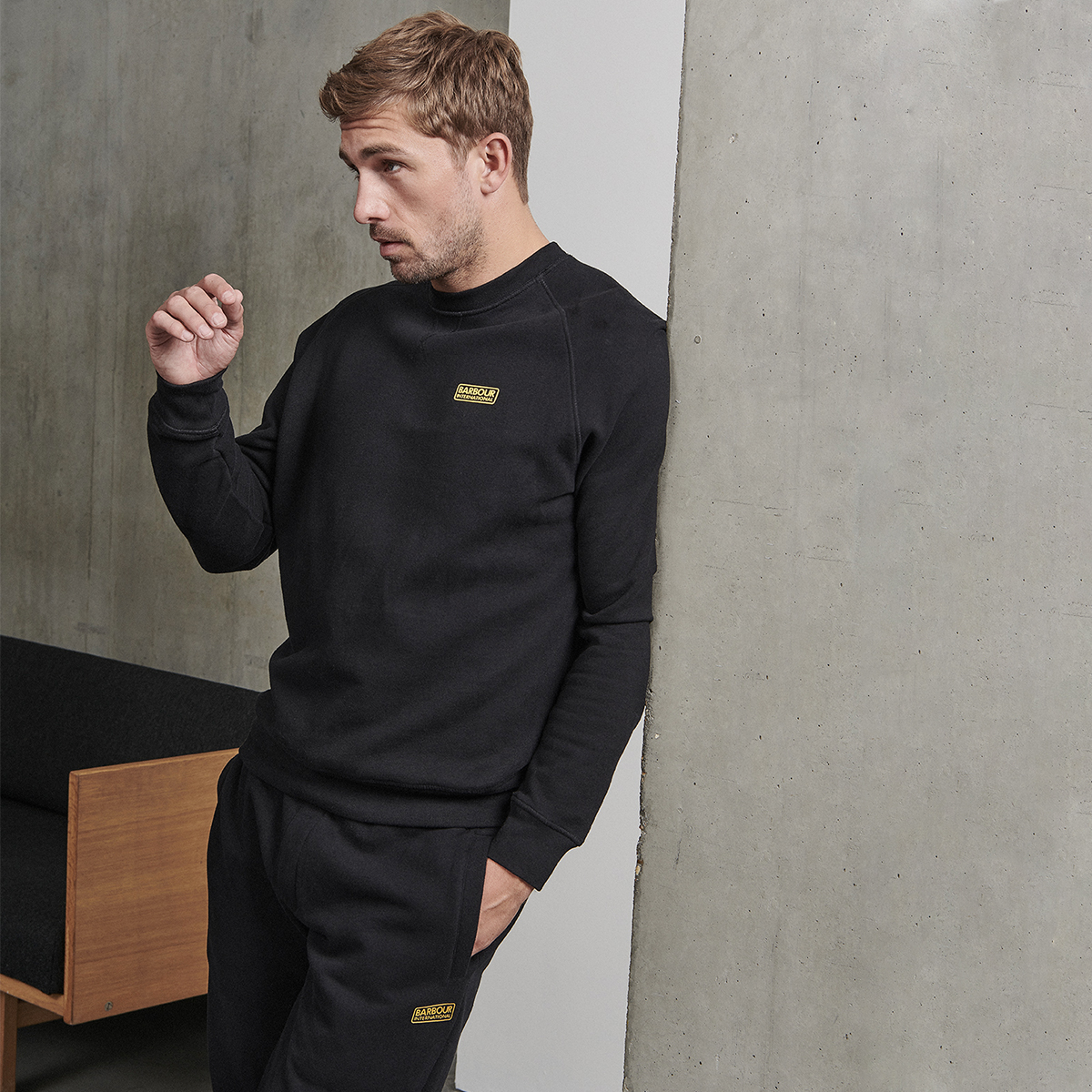 A man dressed in Barbour International joggers and a jumper leaning against a wall
