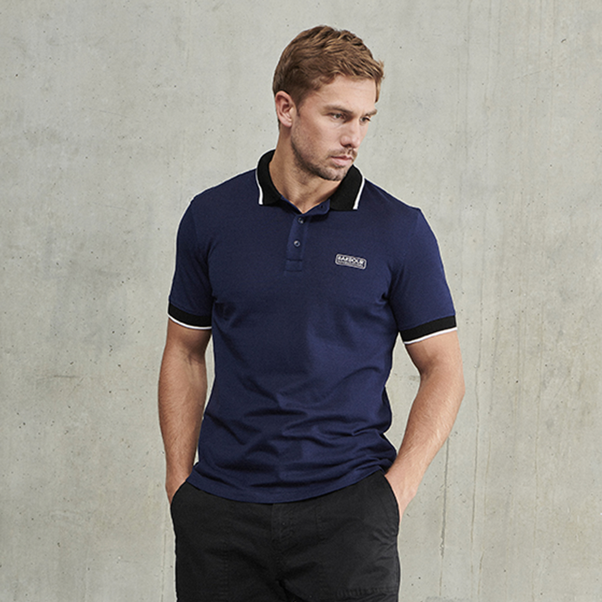 A man wearing a Barbour International polo shirt standing with his hands in his pockets