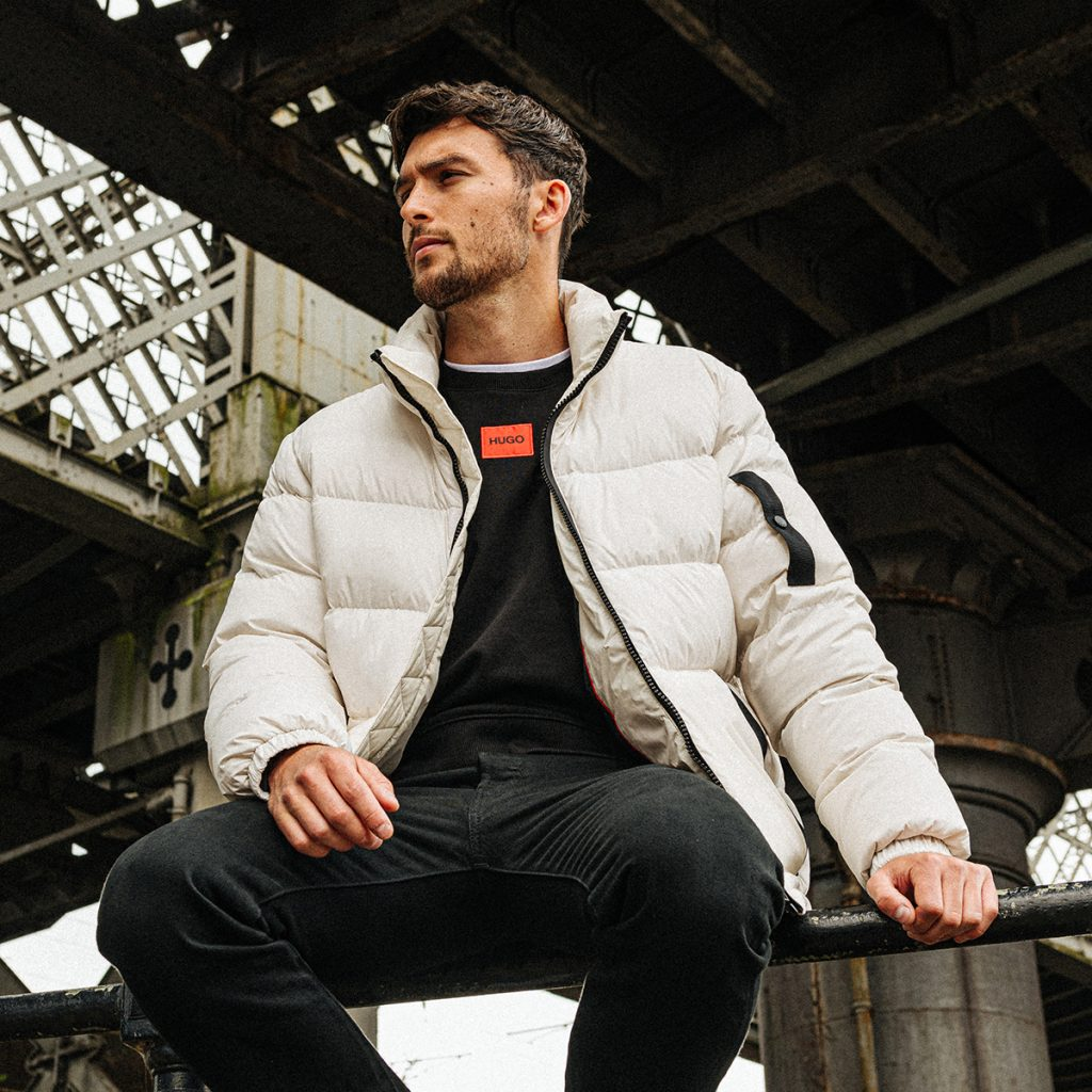A man sitting outside wearing a jacket and layered outfit