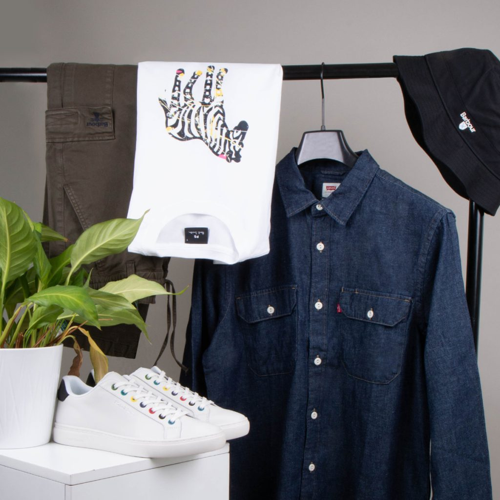 A capsule wardrobe hanging from a clothes rack including a shirt, T-shirt and trousers