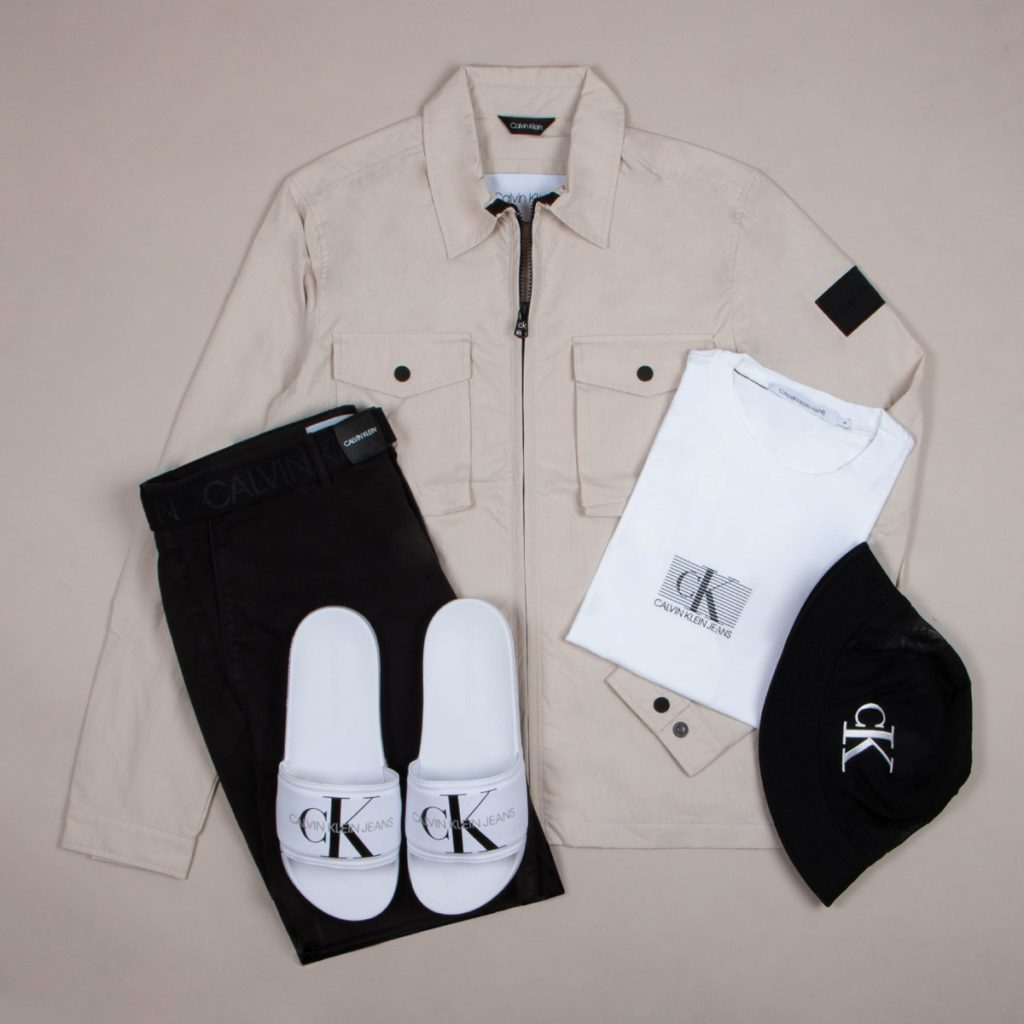 An outfit laid out including a jacket, slides, a T shirt and a hat