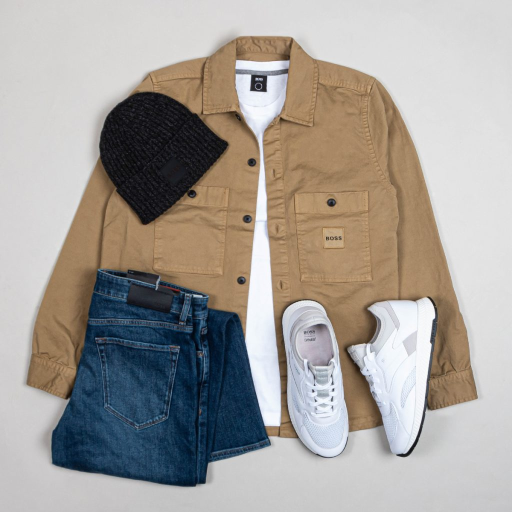 A capsule outfit layout including a coat, jeans, shoes and a hat.
