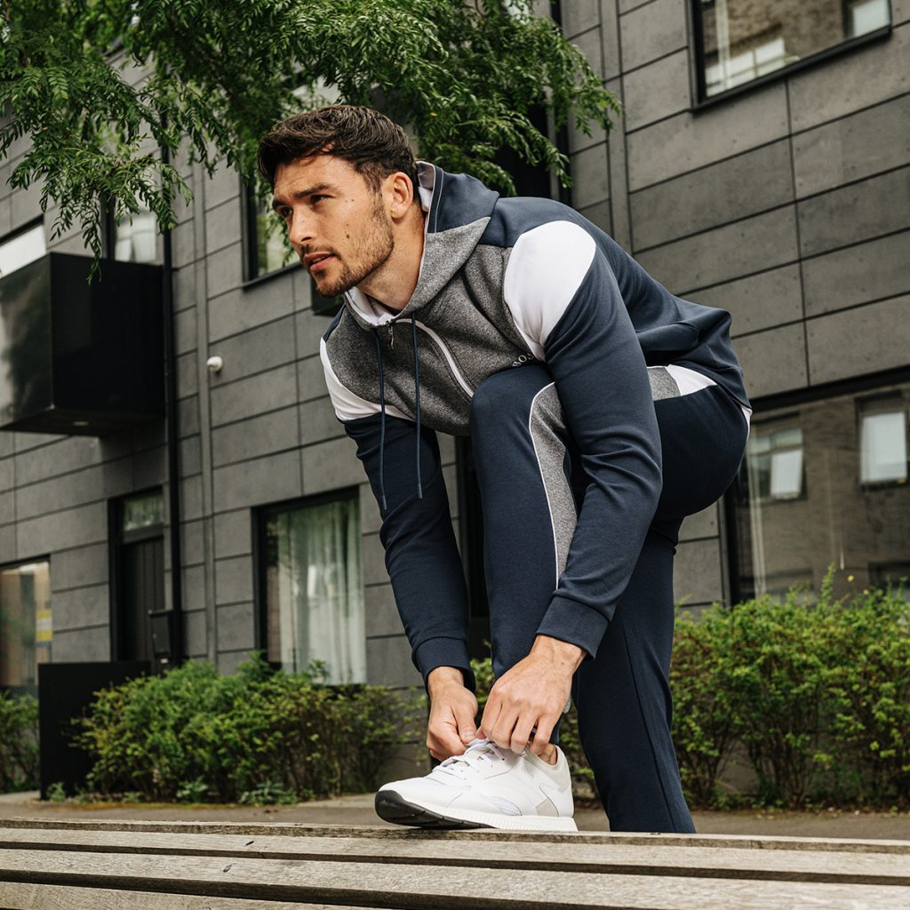 A man dressed in activewear tying his shoelaces
