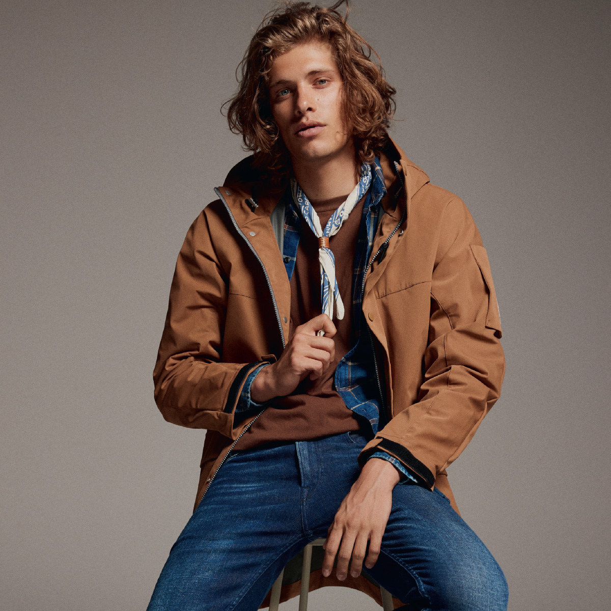 A man dressed in blue Replay jeans and a brown jacket sitting casually on a stool